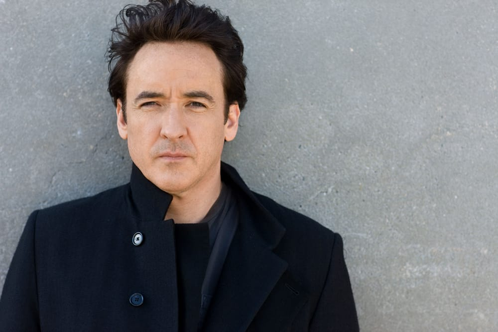 John Cusack wearing a suit and tie smiling at the camera